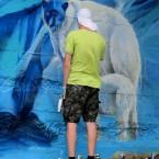 Художник Сергей Шевелев расписывает Дамбу на озере.